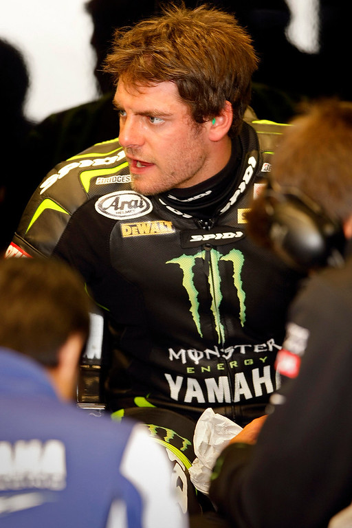 Description of . MotoGp rider Cal Crutchlow from England, talks with his crew in the Monster Yamaha Tech3 garage at Mazda Raceway Laguna Seca during the first day of practice on July 19, 2013.  (Vern Fisher/Monterey County Herald)