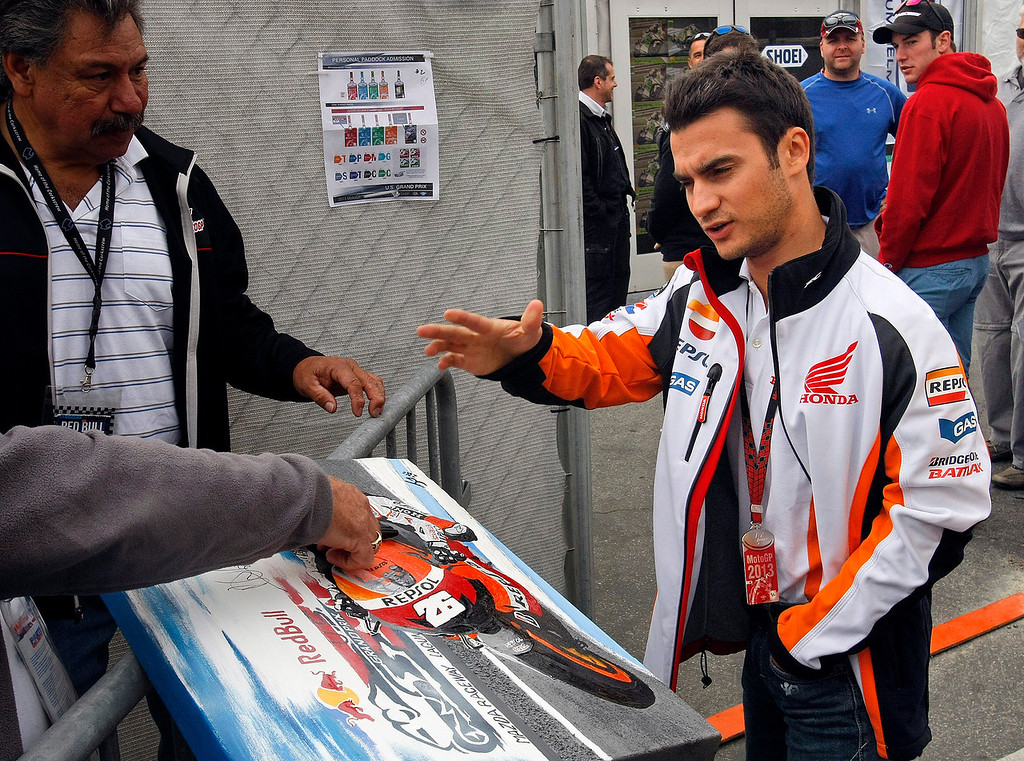 Description of . Injured MotoGp rider Dani Pedrosa from Spain talks with fams points leader Marc Marquez from Spain, talks with fans at Mazda Raceway Laguna Seca during the first day of practice on July 19, 2013.  (Vern Fisher/Monterey County Herald)