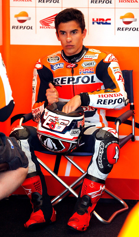 Description of . Current MotoGp points leader Marc Marquez from Spain, talks with his crew in the Repsol Honda Team garage at Mazda Raceway Laguna Seca during the first day of practice on July 19, 2013.  (Vern Fisher/Monterey County Herald)