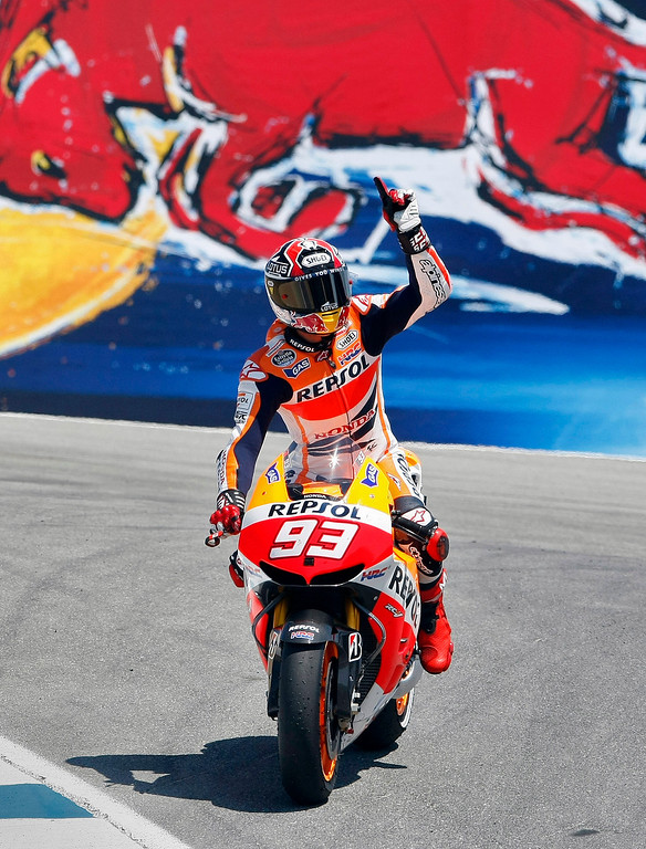 Description of . Marc Marquez from Spain waves to the crowd in the corkscrew at Mazda Raceway Laguna Seca during the Red Bull U.S. Grand Prix in Monterey on July 21, 2013.  Marquez went on to win the race.  (Vern Fisher/Monterey County Herald)