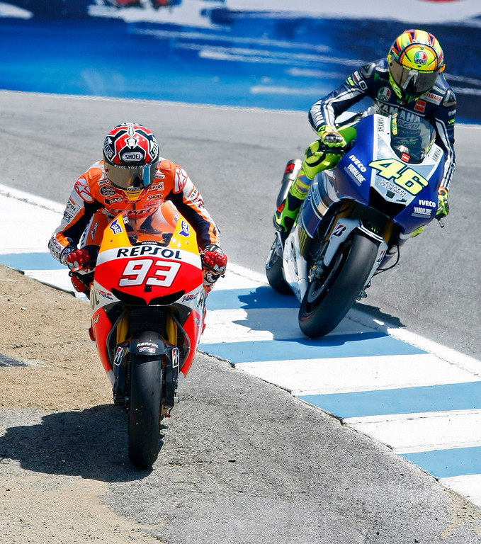 Description of . Marc Marquez from Spain passes Valentino Rossi from Italy in the corkscrew at Mazda Raceway Laguna Seca during the Red Bull U.S. Grand Prix in Monterey on July 21, 2013.  Marquez went on to win the race.  (Vern Fisher/Monterey County Herald)
