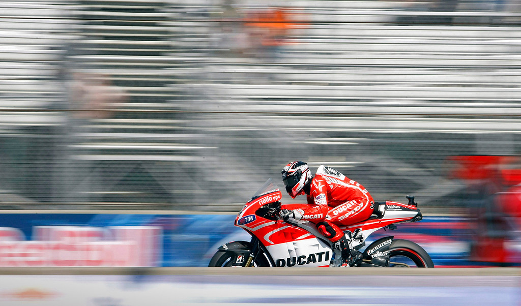 Description of . Andrea Dovizioso from Italy races down the staright on his Ducati at Mazda Raceway Laguna Seca during the morning warm-up session for the Red Bull U.S. Grand Prix in Monterey on July 21, 2013.  (Vern Fisher/Monterey County Herald)