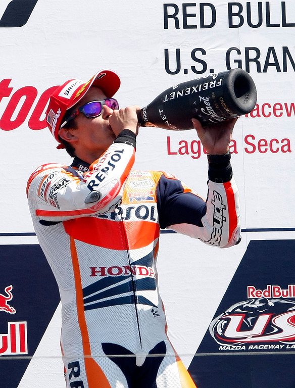 Description of . Marc Marquez from Spain drinks champagne on the winners podium at Mazda Raceway Laguna Seca during the Red Bull U.S. Grand Prix in Monterey on July 21, 2013.  Marquez went on to win the race.  (Vern Fisher/Monterey County Herald)