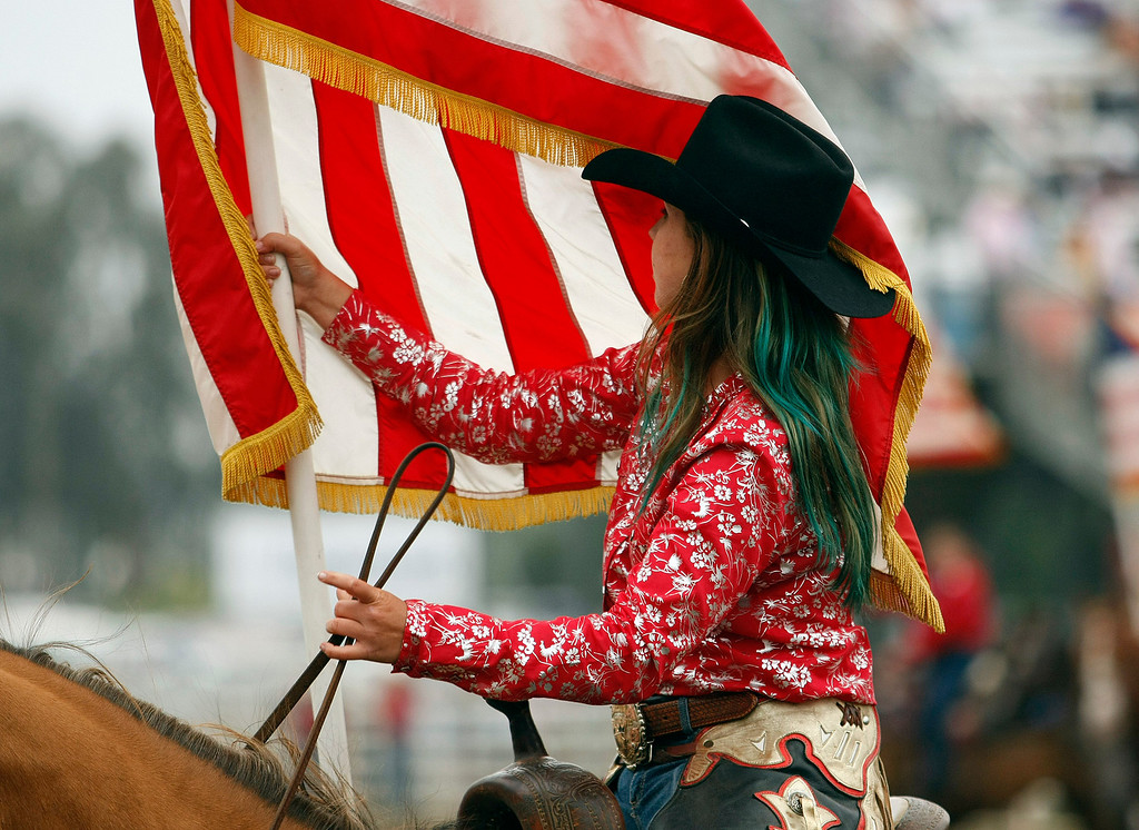 Description of . A rider during the Grand Entry holds the American Flag at the California Rodeo Salinas on July 18, 2013.  (Vern Fisher/Monterey County Herald)