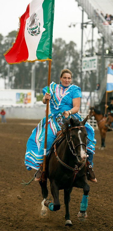 Description of . A rider during the Grand Entry holds the Mexican Flag at the California Rodeo Salinas on July 18, 2013.  (Vern Fisher/Monterey County Herald)