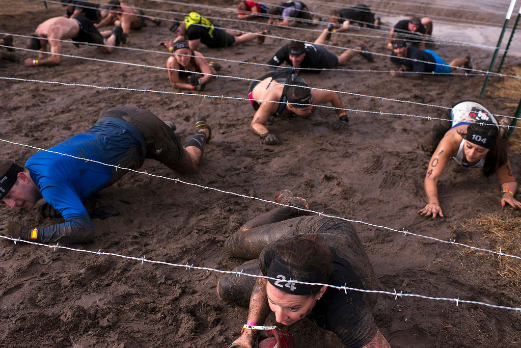 Description of . Spartan Race competitors crawl carefully beneath a barbed wire obstacle Saturday, August 10th, 2013. (Matthew Hintz/Monterey County Herald)