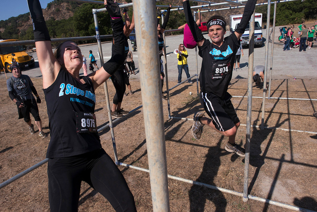 Description of . Tiffany and Reno Ditullo traverse a set of monkey bars Saturday, August 10th, 2013 during the first annual Monterey Spartan Race, which was held this year at Toro Park. (Matthew Hintz/Monterey County Herald)
