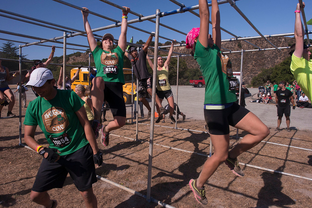 Description of . The Bauger Cove team attacks the monkey bars, Saturday August 10th, 2013, during the first annual Monterey Spartan Race. (Matthew Hintz/Montery County Herald)