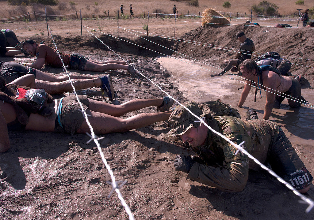 Description of . Some of those who particpated in the grueling Spartan Race, Saturday, August 10th, 2013 crawl through a portion of the almost 13 mile obstacle course.  (Matthew Hintz/Monterey County Herald)