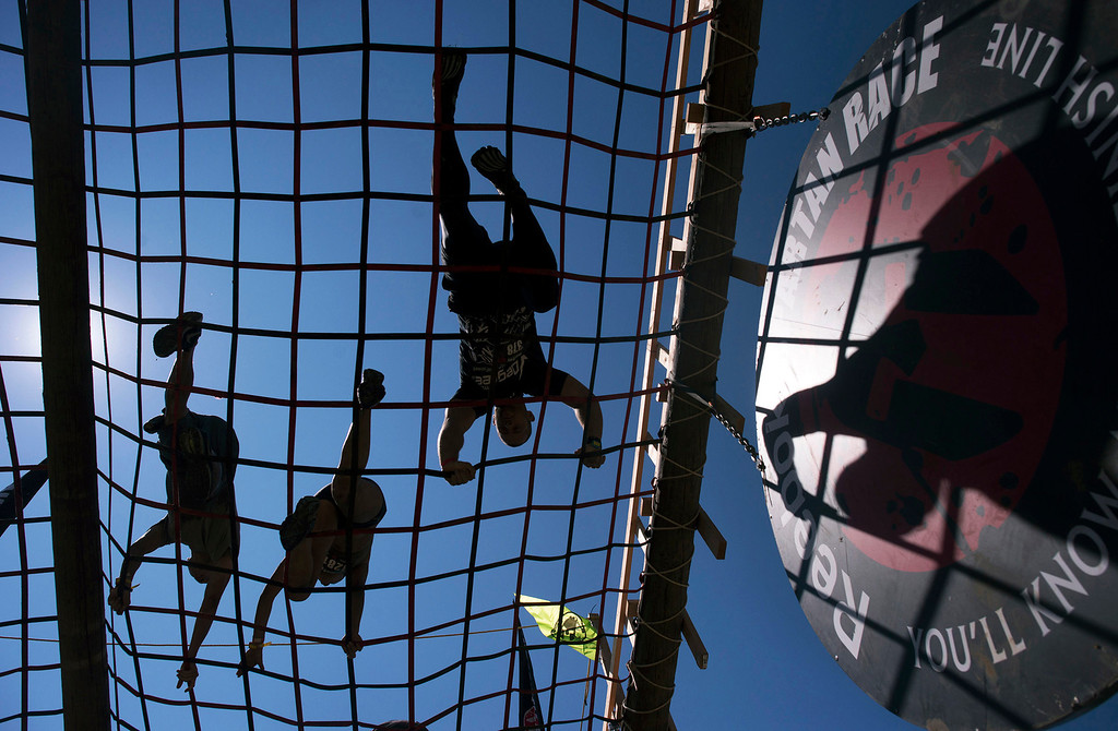 Description of . Racers are silhouetted as they cross an obstacle during the first annual Spartan Race, Saturday, August 10th, 2013 at Toro Park. (Matthew Hintz/Monterey County Herald)