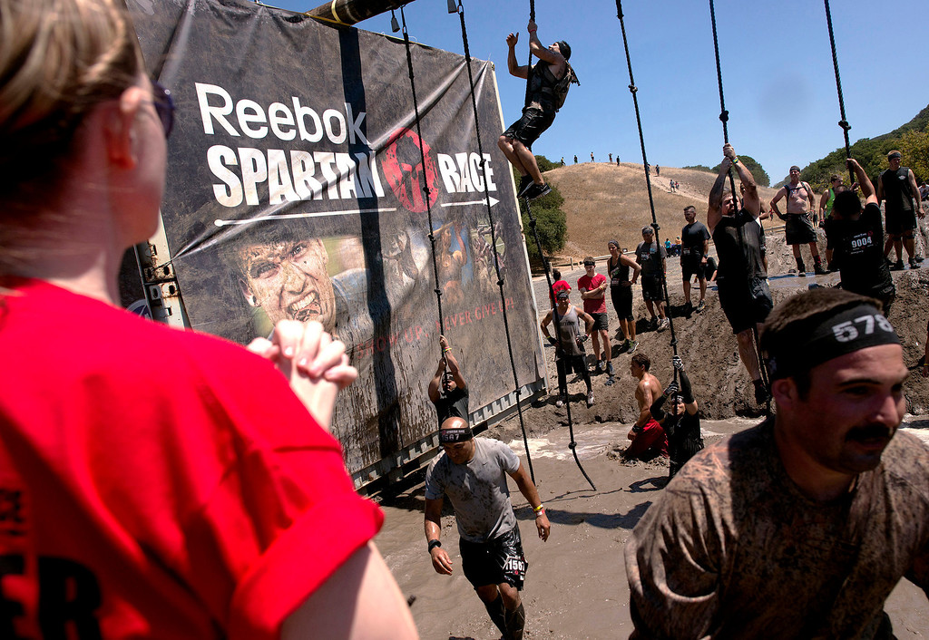 Description of . Jessica Apple, left, looks on as her brother ascends a climbing rope during the first annual Spartan Race at Toro Park Saturday, August 10th, 2013. (Matthew Hintz/Monterey County Herald)
