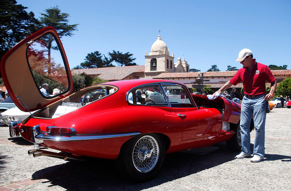 . Ron Avery of Winnetka, Calif. lifts the hood of his 1965 Jaguar E Type while whiping down his vehicle during the Blessing of the Cars at Carmel Mission in Carmel, Calif. on Wednesday August 14, 2013.   (Photo David Royal/ Monterey County Herald)
