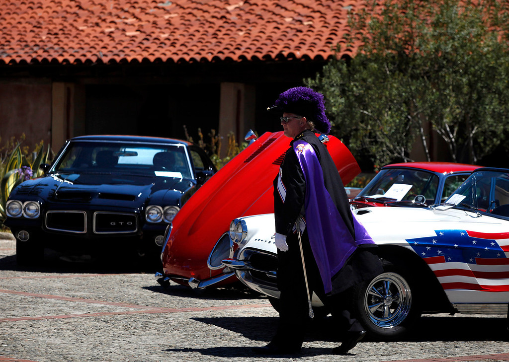 . Knight of Columbus Chris Will walks past a row of cars during the Blessing of the Cars at Carmel Mission in Carmel, Calif. on Wednesday August 14, 2013.   (Photo David Royal/ Monterey County Herald)