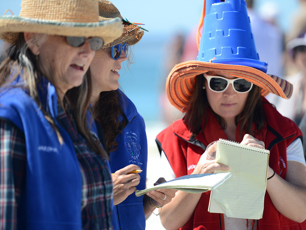 . Sand castle judges Catherine Hawley, from right, wears a bucket on her head while judging with her sister in law Merritt Hawley and Terry Dahl on Carmel Beach in Carmel, Calif. on Sunday September 15, 2013. (Photo David Royal/ Monterey County Herald)