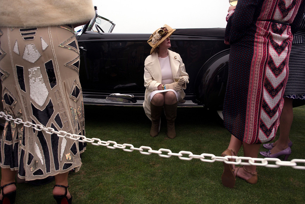 . Margie Cassini, sits on the fender of her and her husband, Joseph Cassini\'s 1934 Packard Victoria Dietrich Sunday, August 18th, 2013 at the Concours d\'Elegance luxury automobile show. The Cassini\'s Packard went on to win Best in Show. (Matthew Hintz/Monterey County Herald)