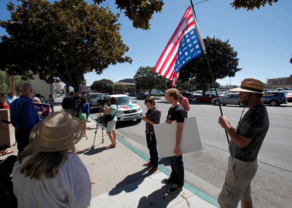 . Mark Reed (with flag) participates with the Peace Coalition of Monterey County in a demonstration in Salinas on September 4, 2013 against possible US military action in Syria.  (Vern Fisher/Monterey County Herald)