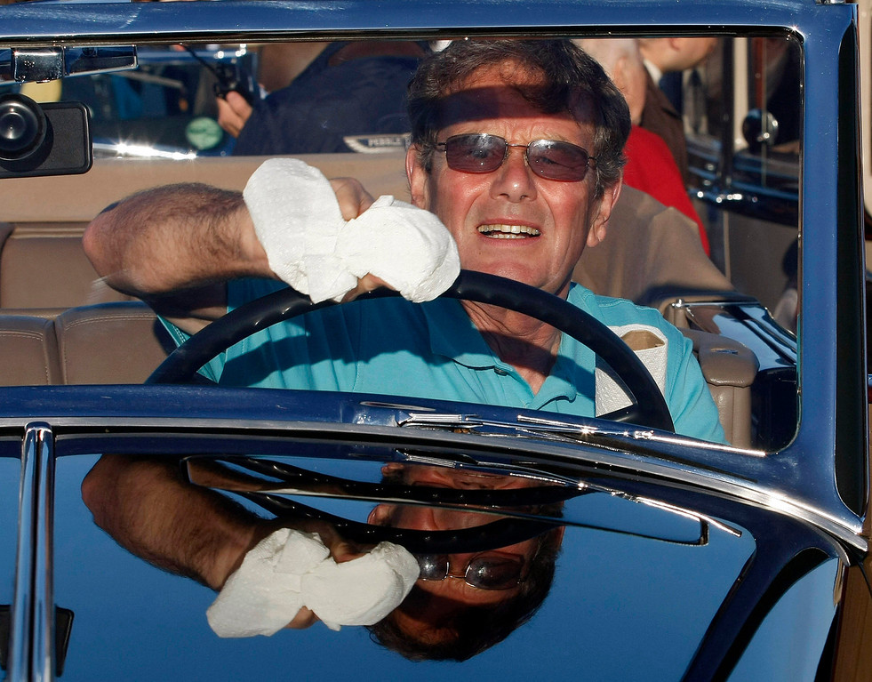 . Ralph Curzon cleans the windshield of a 1933 Cadillac V16 prior to the start of the Tour d\'Elegance on August 15, 2013.  (Vern Fisher/Monterey County Herald)