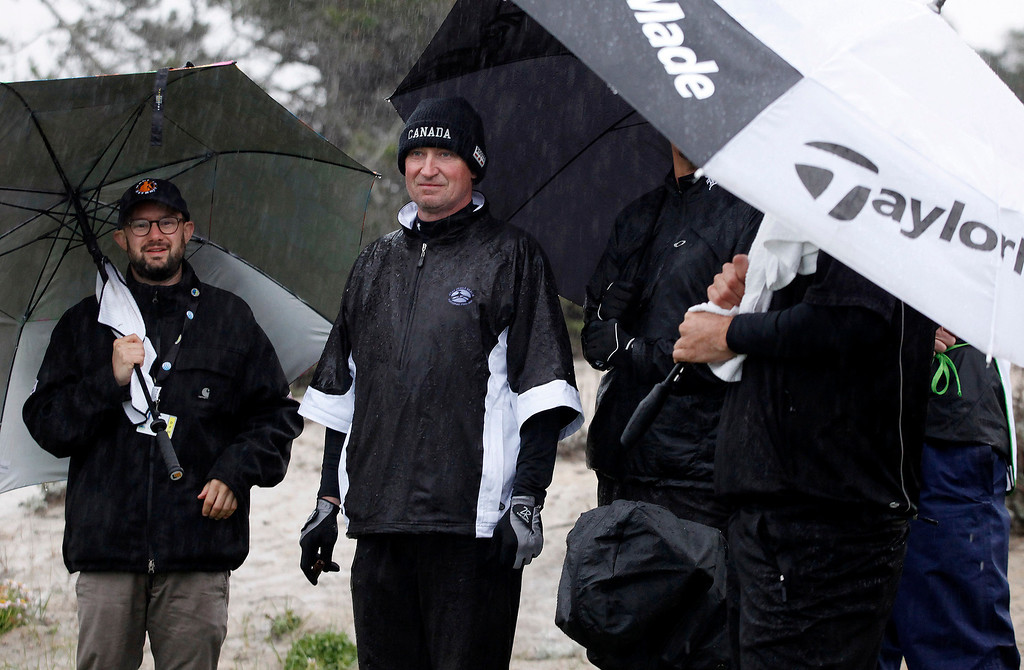 . Wayne Gretzky takes cover from the rain at Spyglass Hill Golf Course during the first round of the AT&T Pebble Beach National Pro Am on Feb. 6, 2014.  (Vern Fisher/Monterey County Herald)