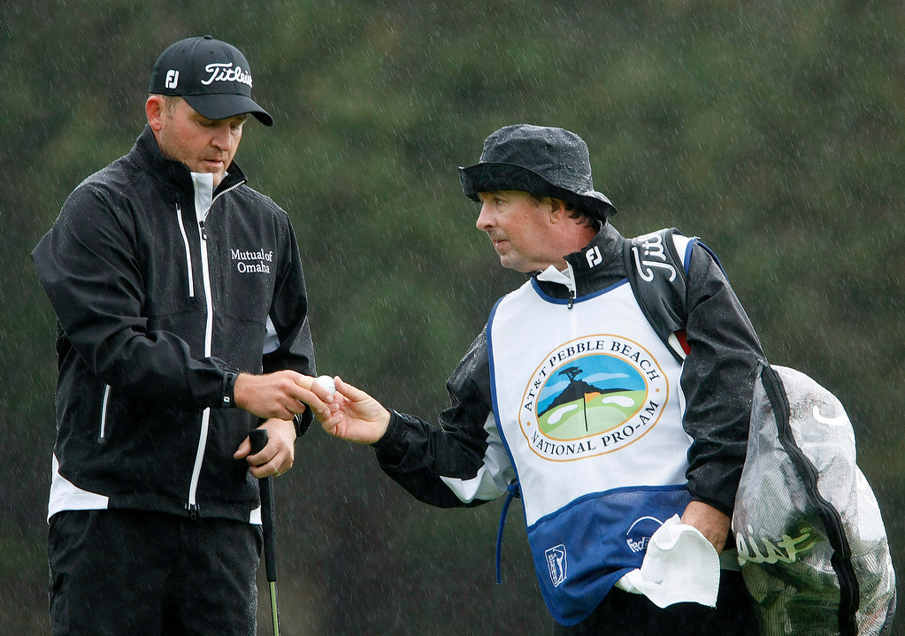 . PGA pro Jason Bohn and caddy in the rain at Spyglass Hill Golf Course during the first round of the AT&T Pebble Beach National Pro Am on Feb. 6, 2014.  (Vern Fisher/Monterey County Herald)