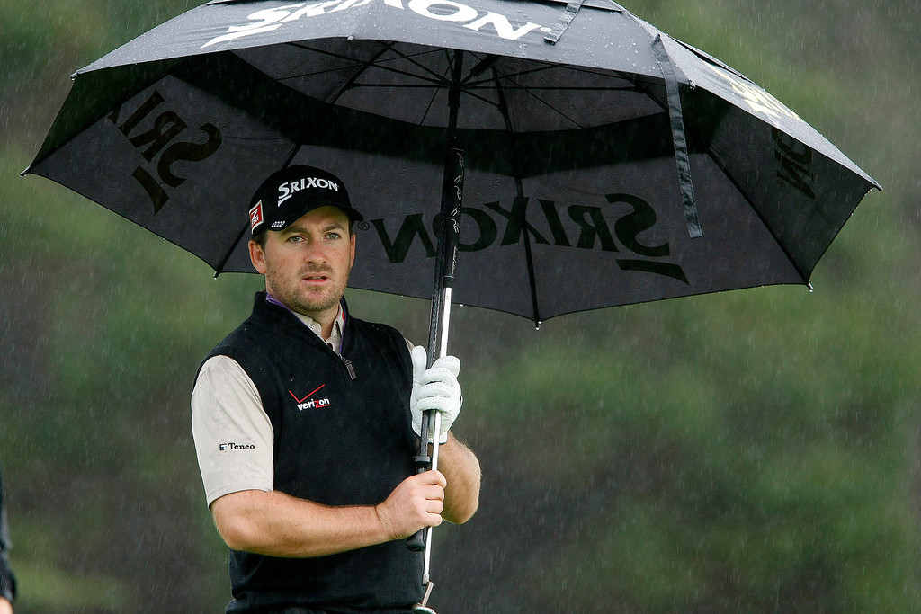 . Graeme McDowell takes cover from the rain at Spyglass Hill Golf Course during the first round of the AT&T Pebble Beach National Pro Am on Feb. 6, 2014.  (Vern Fisher/Monterey County Herald)
