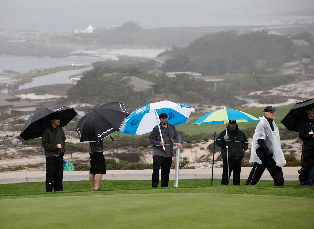 . The gallery on the 2nd hole takes cover from the rain at Spyglass Hill Golf Course during the first round of the AT&T Pebble Beach National Pro Am on Feb. 6, 2014.  (Vern Fisher/Monterey County Herald)