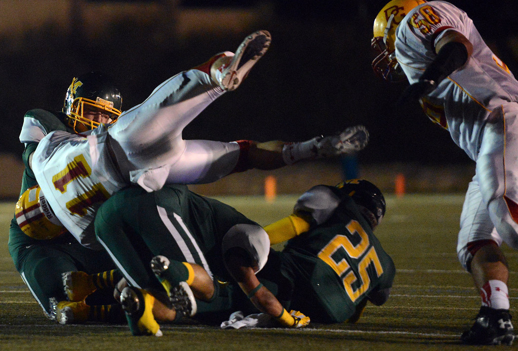 . Pacific Grove\'s Dylan Chesney is upended by Monterey defenders on a run during football in Monterey, Calif. on Friday September 20, 2013.  (Photo David Royal/ Monterey County Herald)