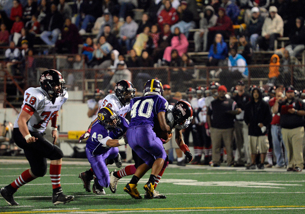 . Seaside quarterback Lorenzo Johnsonis taken down by Salinas\' Jeremiah Garcia and Nicholas Fierros during football at Salinas on Friday October 18, 2013. (Photo David Royal/ Monterey County Herald)
