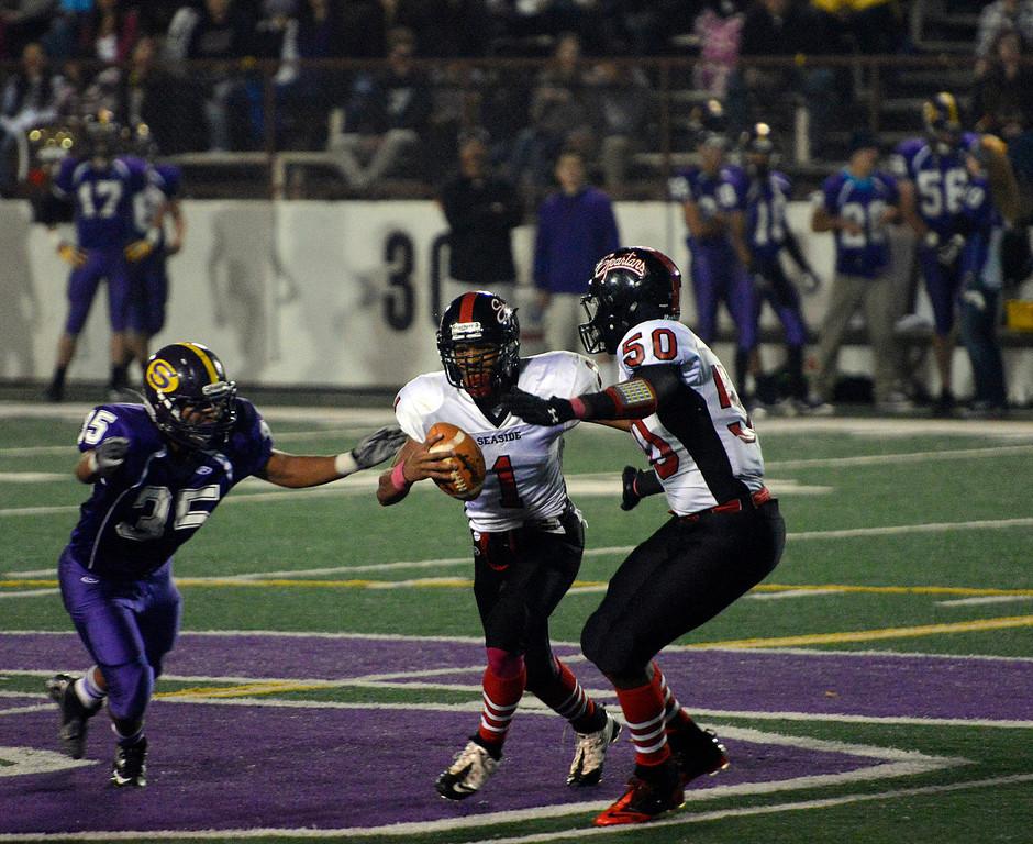 . Seaside quarterback Lorenzo Johnson is caught by Salinas\' Sergio Guzman during football at Salinas on Friday October 18, 2013. (Photo David Royal/ Monterey County Herald)