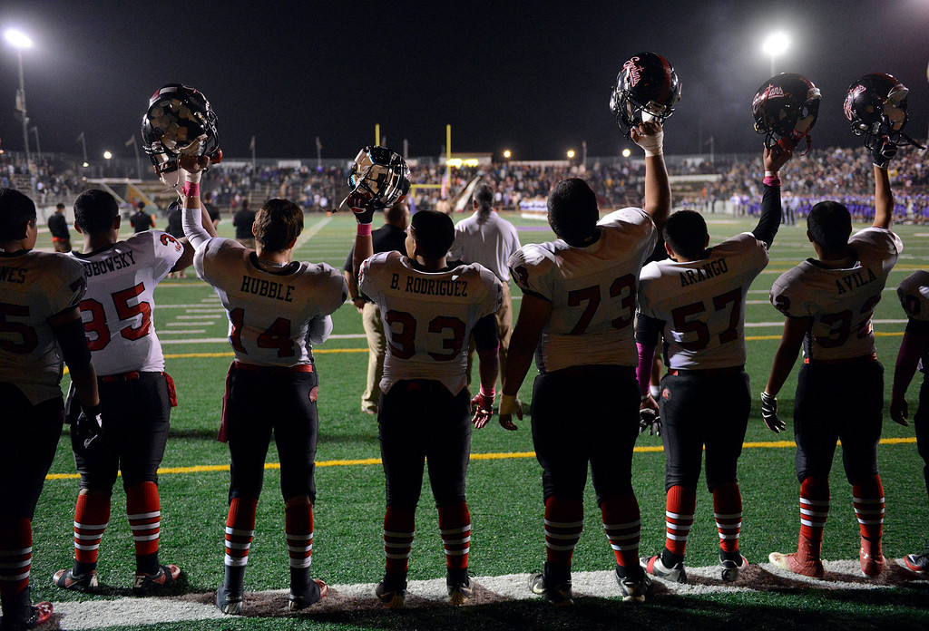 . Seaside players hold their helmets in the air as the National Anthem is completed before football at Salinas on Friday October 18, 2013. (Photo David Royal/ Monterey County Herald)