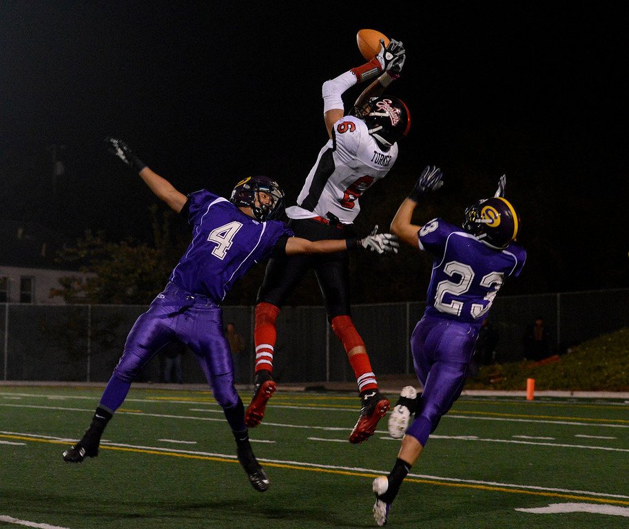 . Seaside\'s Ronald Turner reels in a touchdown pass over Salinas\' Jorge Gomez-Soto, left, and Vince LaSala during football at Salinas on Friday October 18, 2013. (Photo David Royal/ Monterey County Herald)