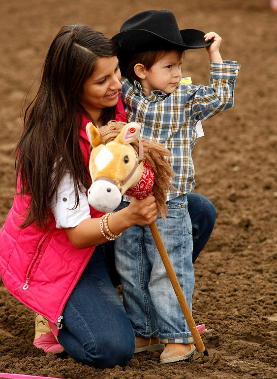 ". Melina Campa gets her son Xavier Campa, 3, ready for some ""stick horse\"" races at the California Rodeo Salinas on July 18, 2013.  (Vern Fisher/Monterey County Herald)"