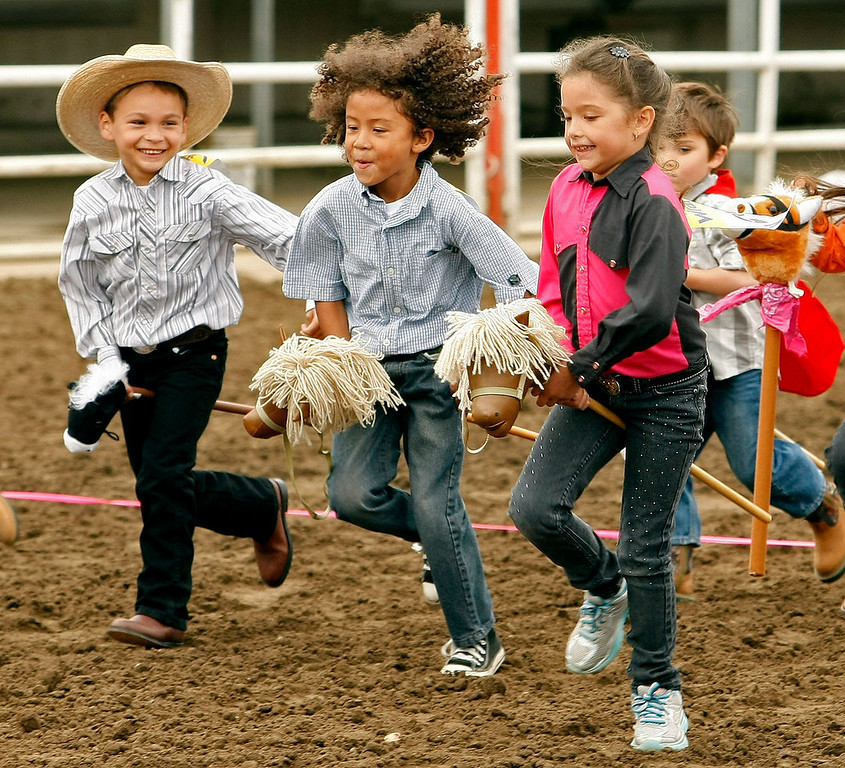 . Kids battle it out during the stick horse races at the California Rodeo Salinas on July 18, 2013.  (Vern Fisher/Monterey County Herald)