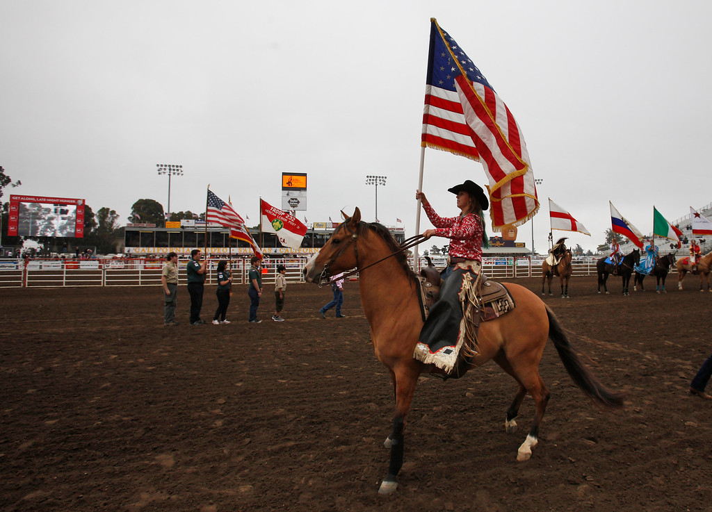 . A rider during the Grand Entry holds the American Flag at the California Rodeo Salinas on July 18, 2013.  (Vern Fisher/Monterey County Herald)