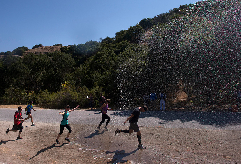. Racers needing to cool down during the Spartan Race run for the hose, Saturday, August 10th, 2013. (Matthew Hintz/Monterey County Herald)