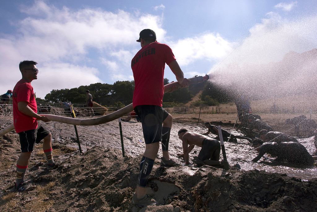 . Spartan Race event staff douse racers with a firehose as they crawl beneath barbed wire Saturday, August 10th, 2013 at Toro Park. (Matthew Hintz/Monterey County Herald)